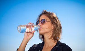 Chica jóven bebiendo agua de Fuentes de Arganda para hidratarse en verano