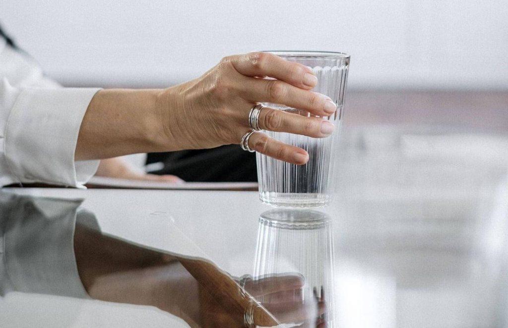 Mujer sugetando un baso de agua mineral de Fuentes de agua Arganda